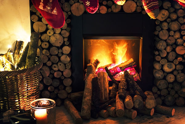 A log fireplace with Christmas stocking hanging on the mantle and a basket of logs and a candle on the side.