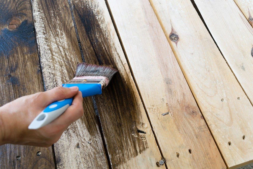 Someone staining a deck with a blue paint brush. Both stain and paint entail their own distinct benefits and drawbacks.